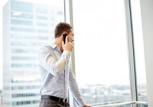Man on phone looking out office window
