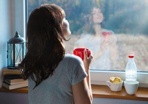 Young woman holding cup of coffee sitting home by the window. F