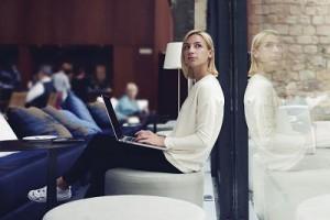 Thoughtful female sitting by internet cafe windows